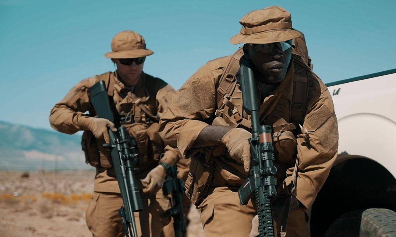 Żołnierze podczas patrolu w pełnym oporządzeniu chowający się za samochodem