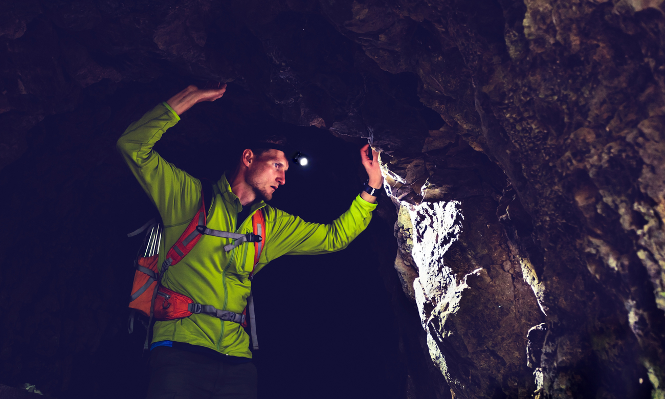 Człowiek w jaskini z latarką