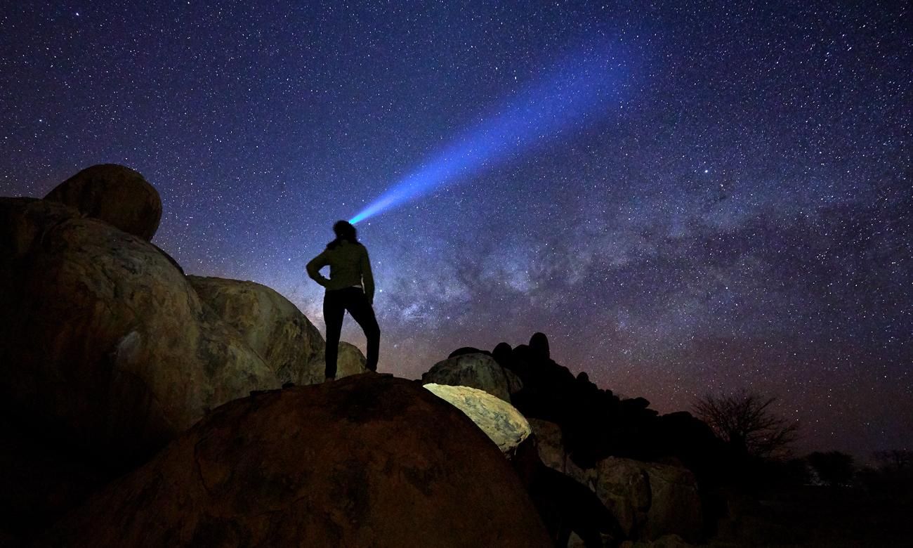 Człowiek w górach z latarką Black Diamond Spot 325 Sand