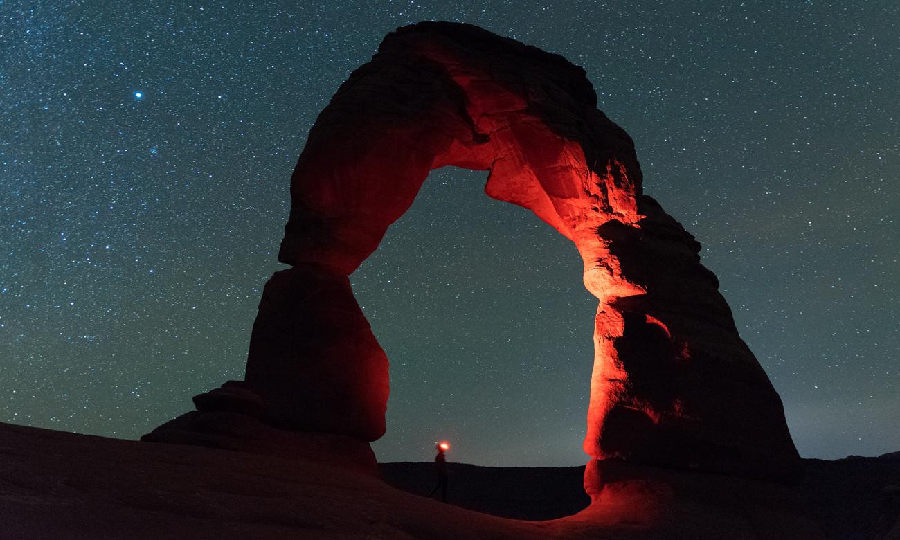 Człowiek na pustyni z latarką Black Diamond Spot 325 Sand