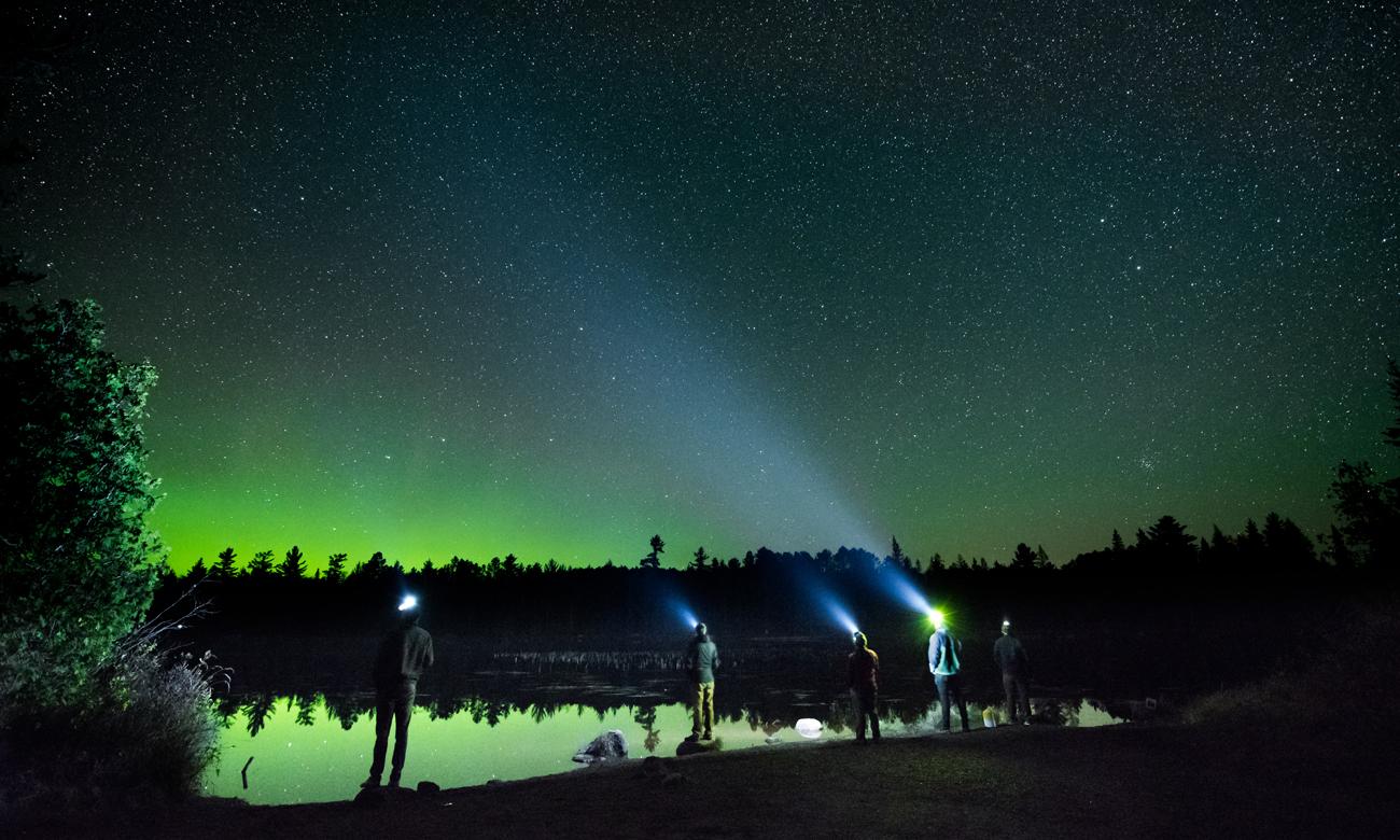 Grupa ludzi nad jeziorem z latarkami