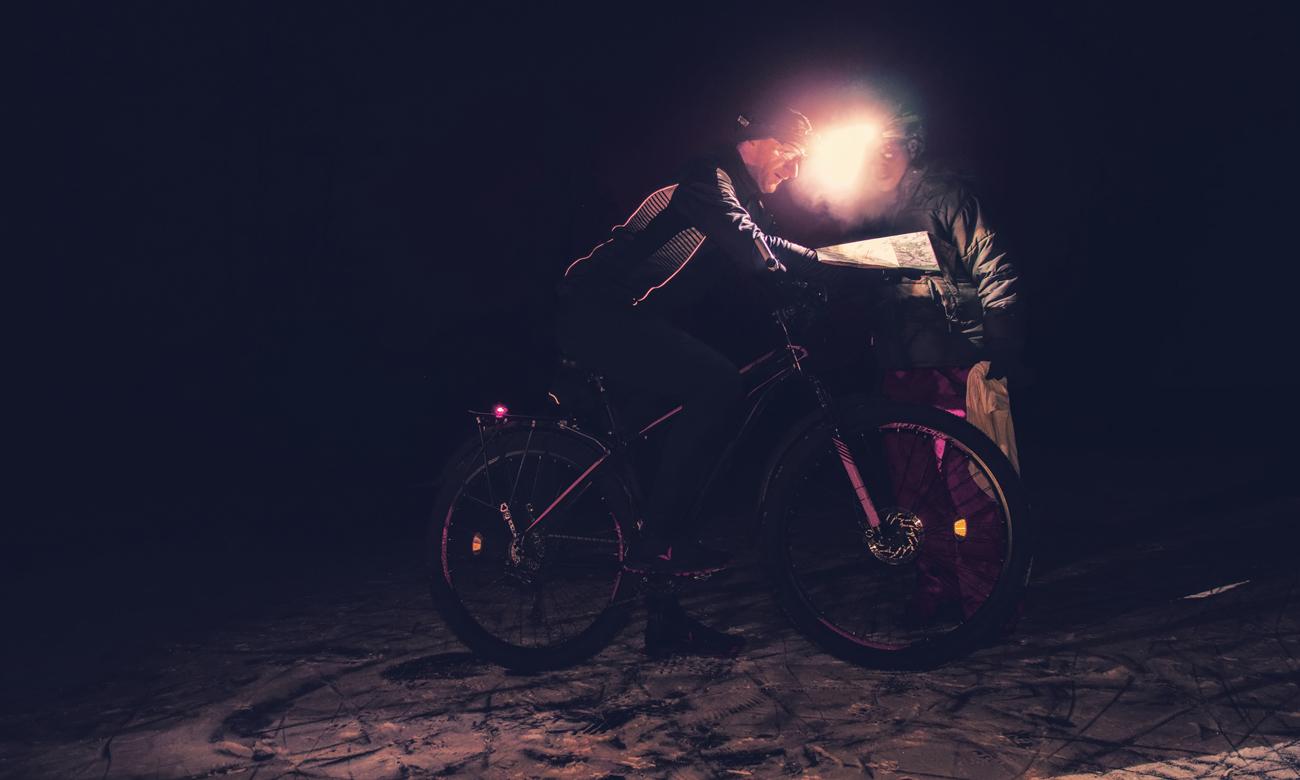 Człowiek na rowerze w nocy z latarką czołową