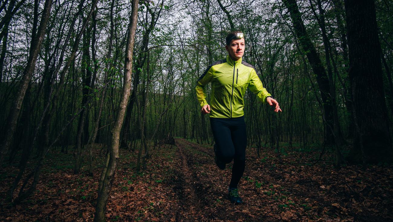 Człowiek biegnący z czołówką przez las