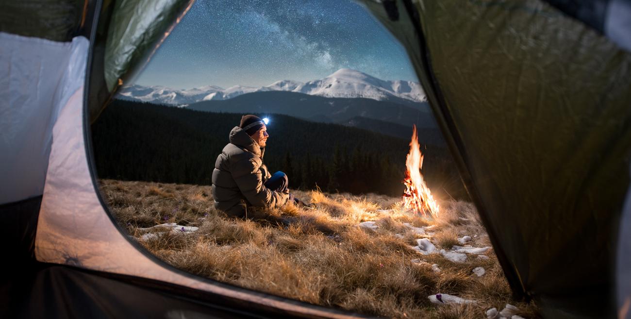 Kobieta z latarką przy namiocie