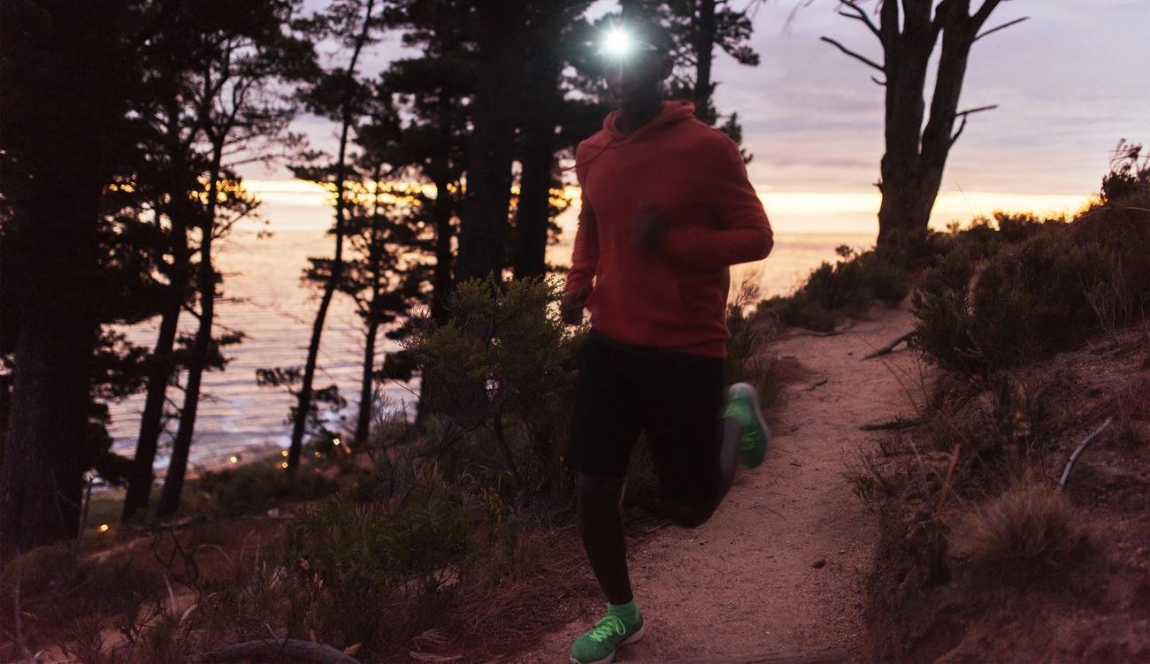Mężczyzna biegnie z czołówką