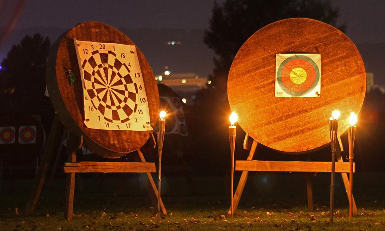 Drewniane tarcze do rzutek oświetlone pochodniami