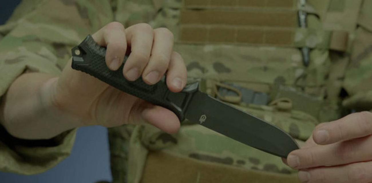Nóż z głownią stałą Gerber Gear Strongarm Coyote FE w dłoni żołnierza