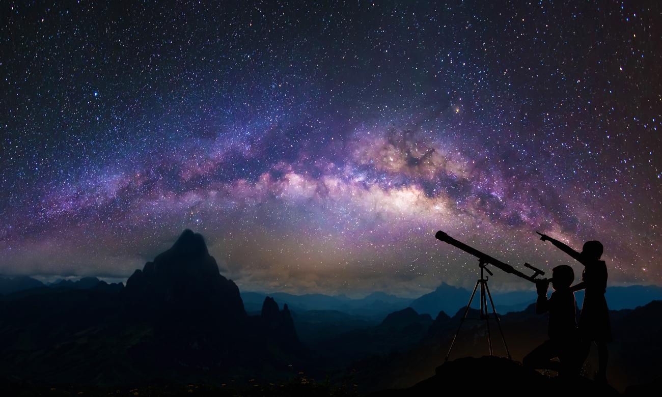 Teleskop i dwoje ludzi obserwujących gwiazdy