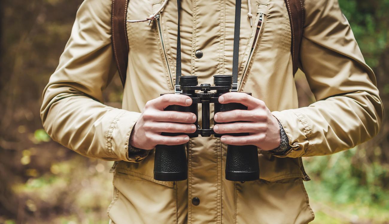 Osoba trzymająca lornetkę na pasie
