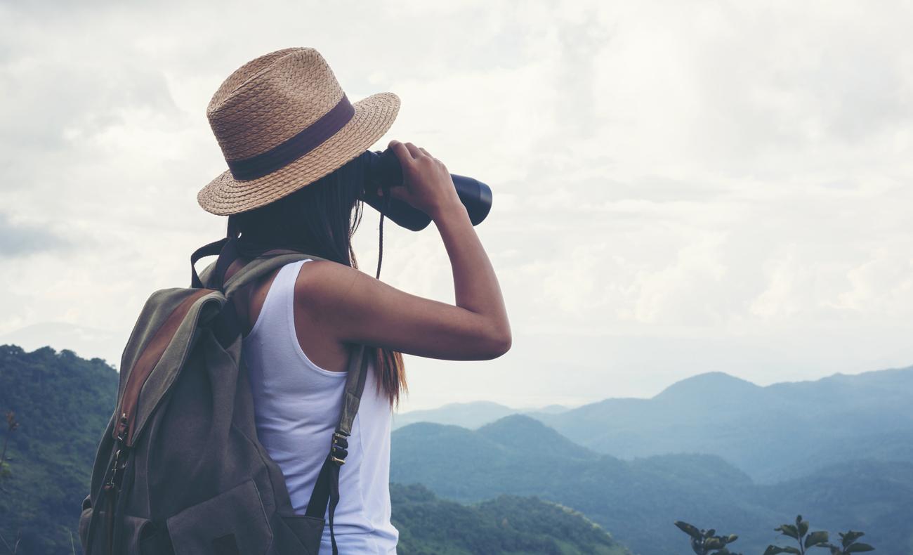 Kobieta obserwuje niebo przez lornetkę