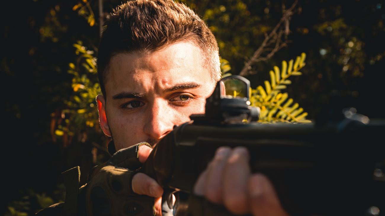 Mężczyzna z przymocowanym do broni kolimatorem