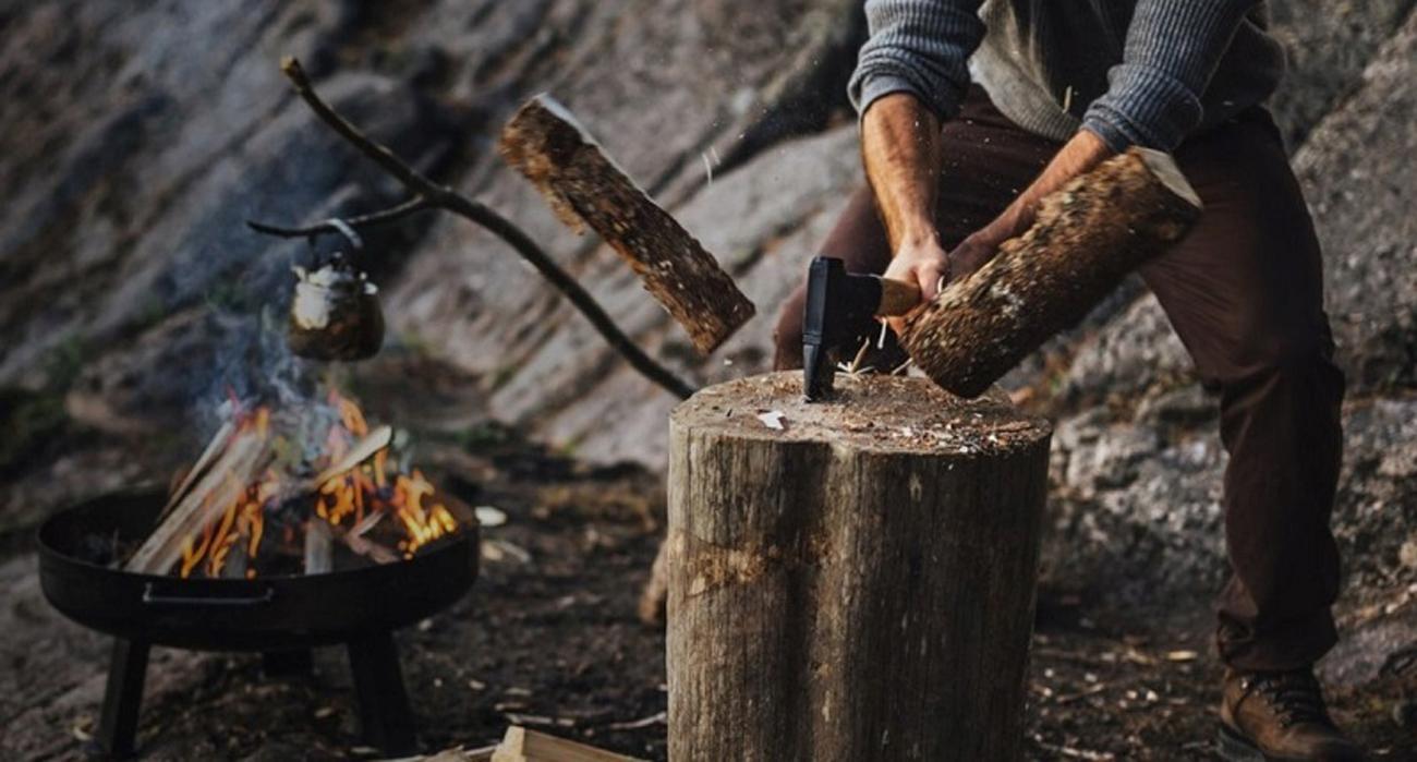 Mężczyzna rozłupujący bloki drewna na opał