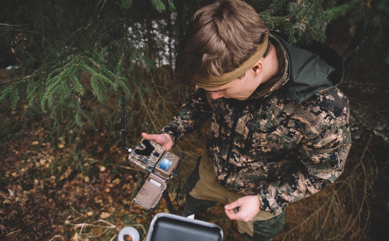 Mężczyzna instalujący fotopułapkę w lesie