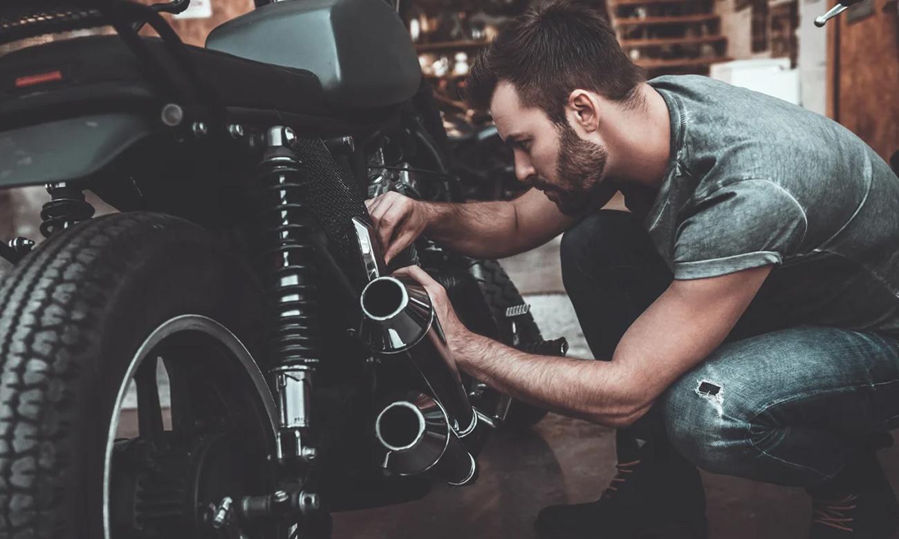 Mężczyzna naprawiający motocykl w garażu