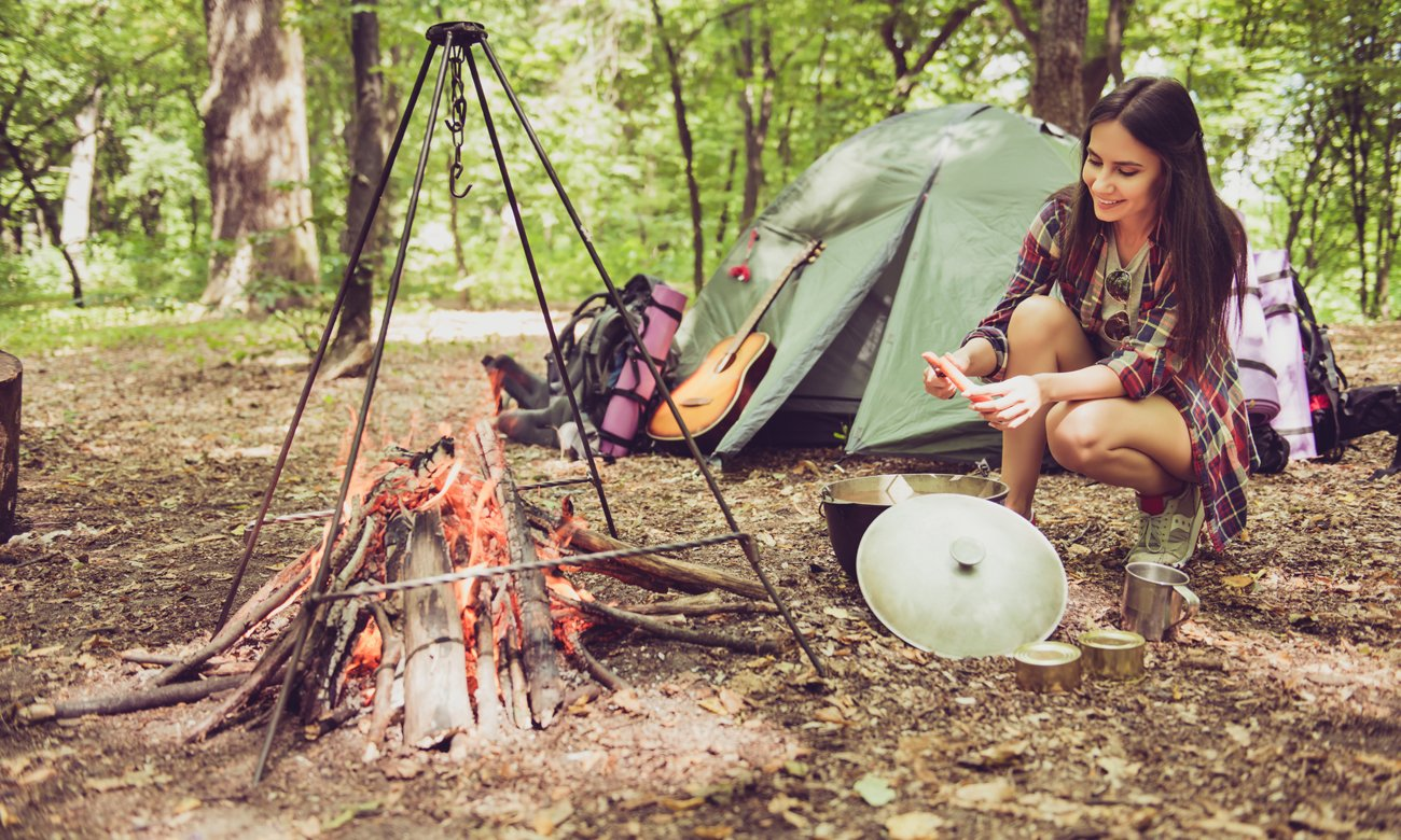 Kobieta przy ognisku przygotowująca posiłek