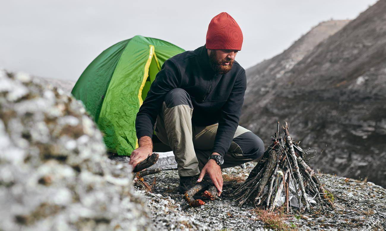 Mężczyzna rozpalający ognisko w górach przed swoim namiotem