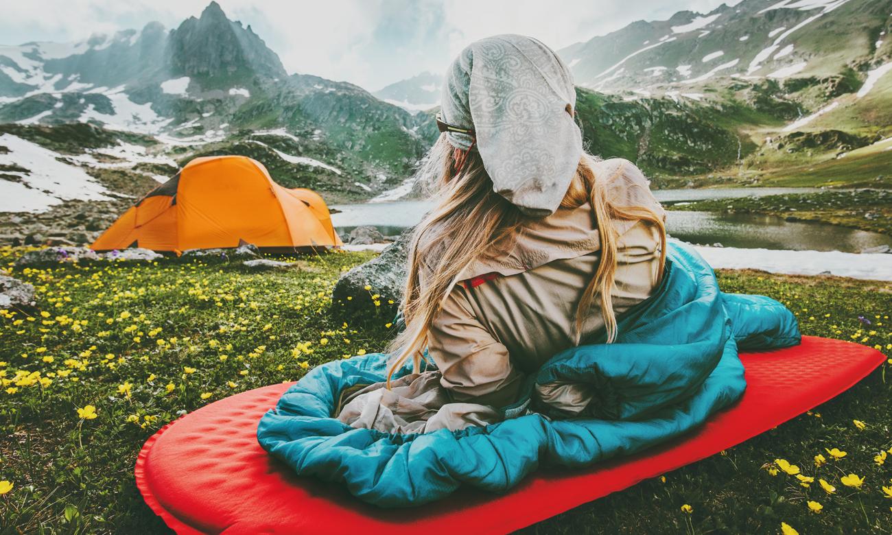 Kobieta w górach leżąca na materacu