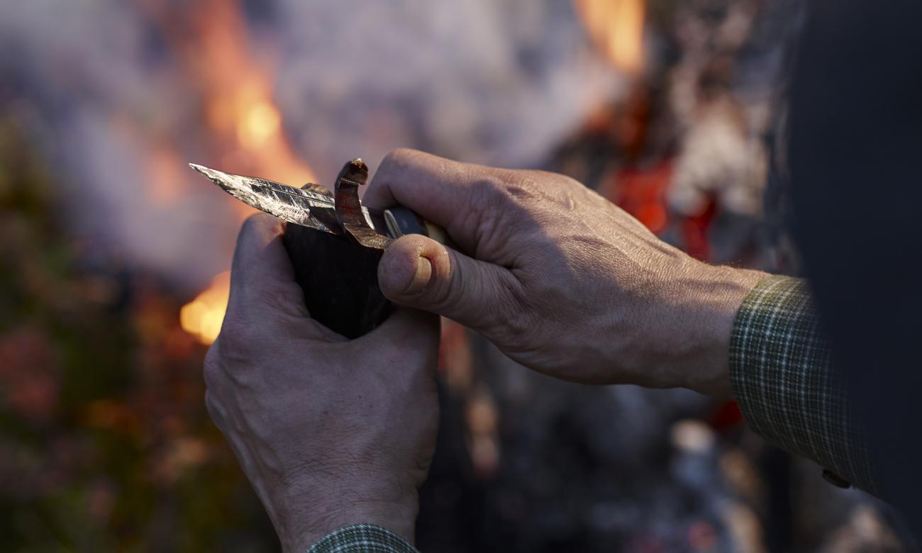 Człowiek przy ognisku z nożem