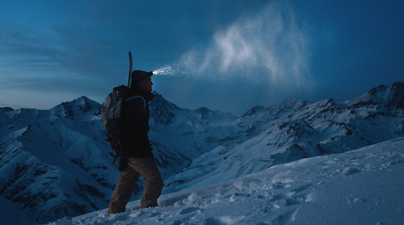 Mężczyzna spacerujący po górach w śniegu