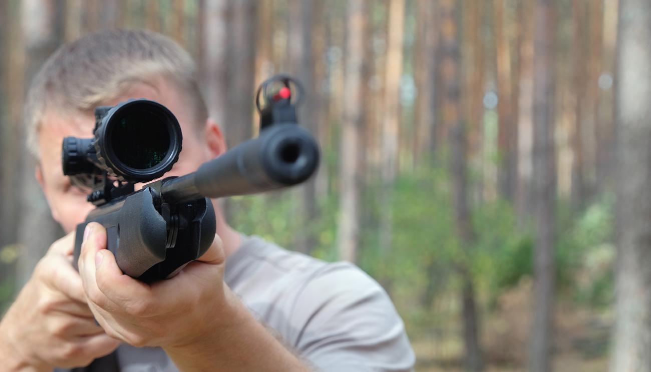 Mężczyzna w lesie strzelający w wiatrówki