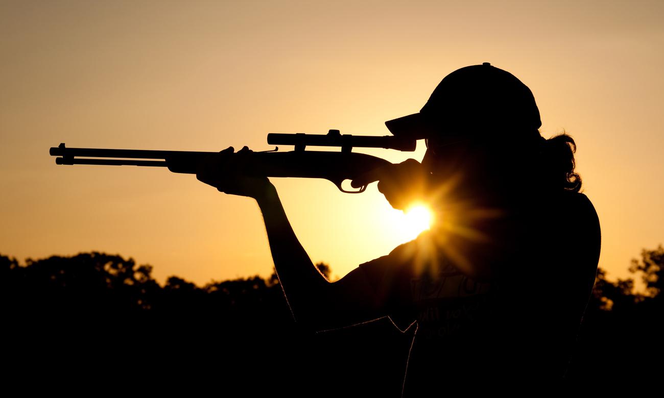 Człowiek z bronią na tle słońca
