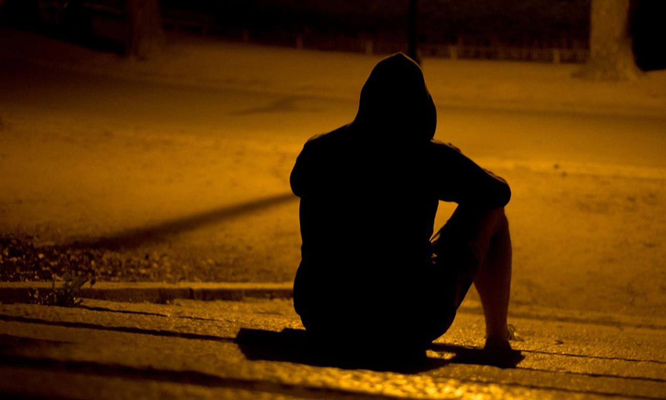 Człowiek siedzący na schodachw nocy