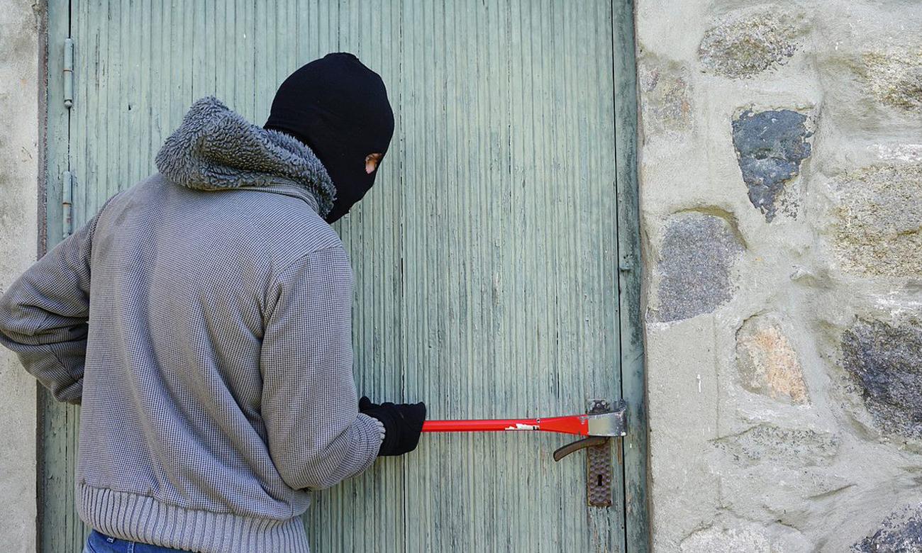 Włamywacz w kominiarce włamujący się do domu
