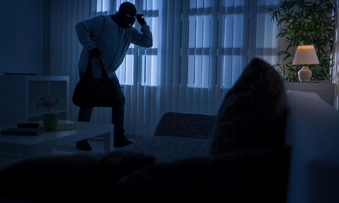 Włamywacz w domu z latarką