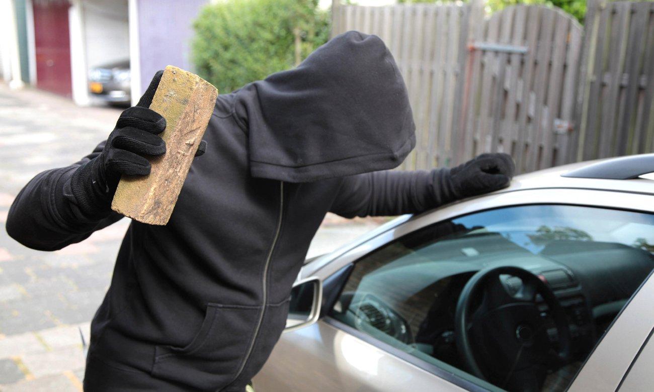 Złodziej włamujący się do samochodu z cegłą w dłoni