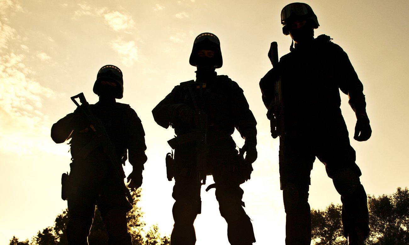Trzech mężczyzn w oporządzeniu z bronią