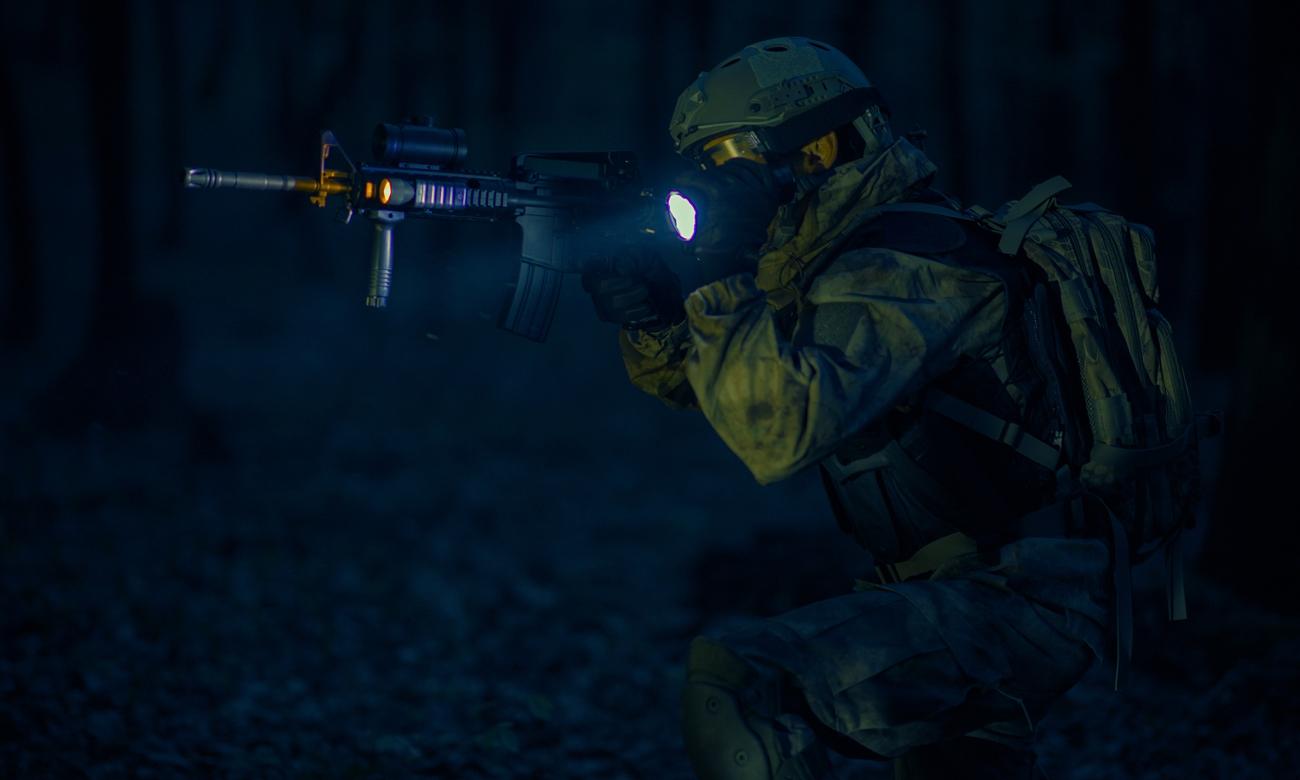 Żołnierz w nocy w lesie z bronią