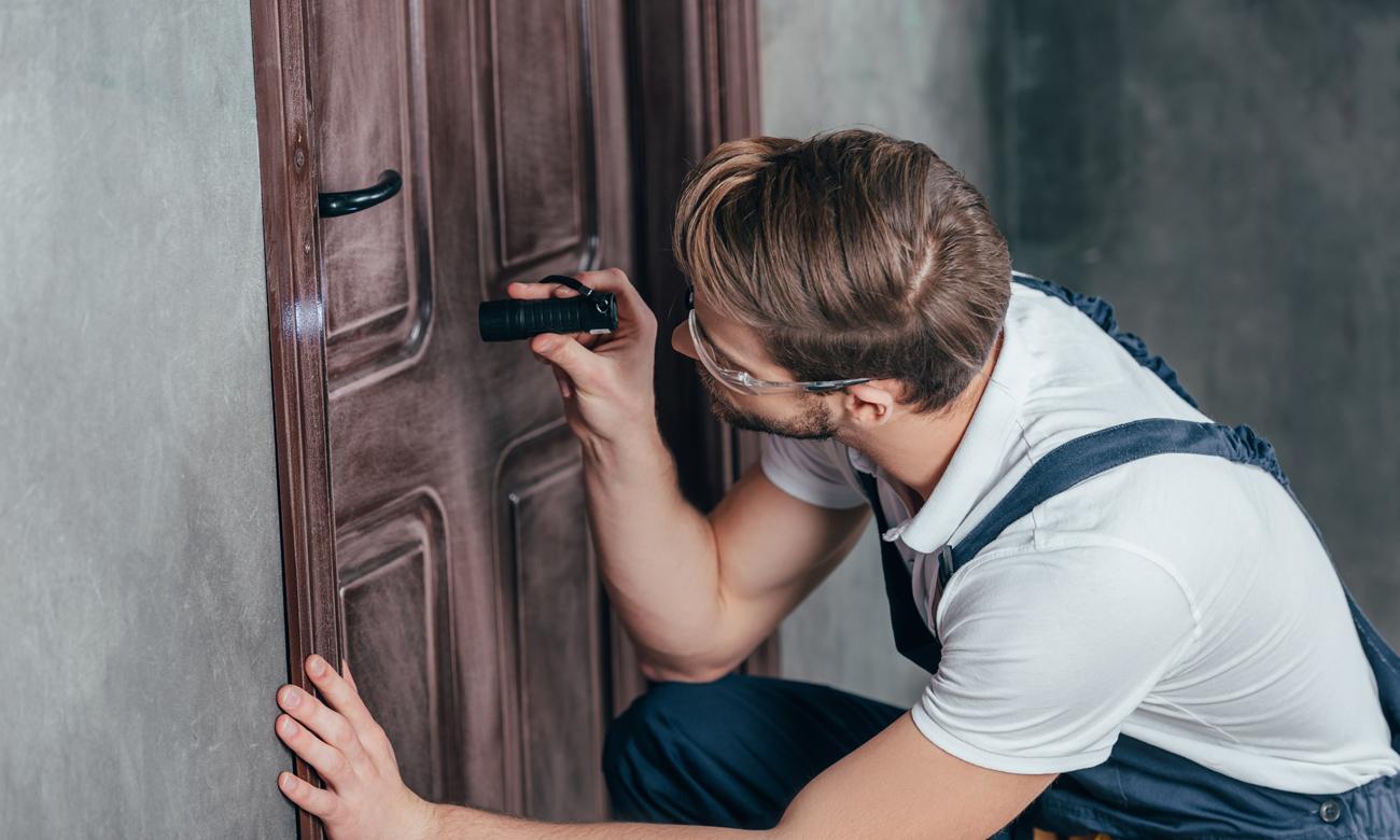 Mężczyzna naprawiający drzwi z latarką