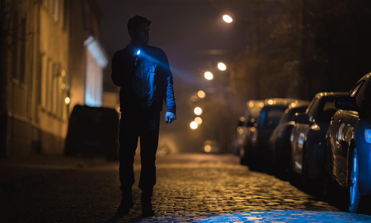 Człowiek z latarką na ciemnej ulicy