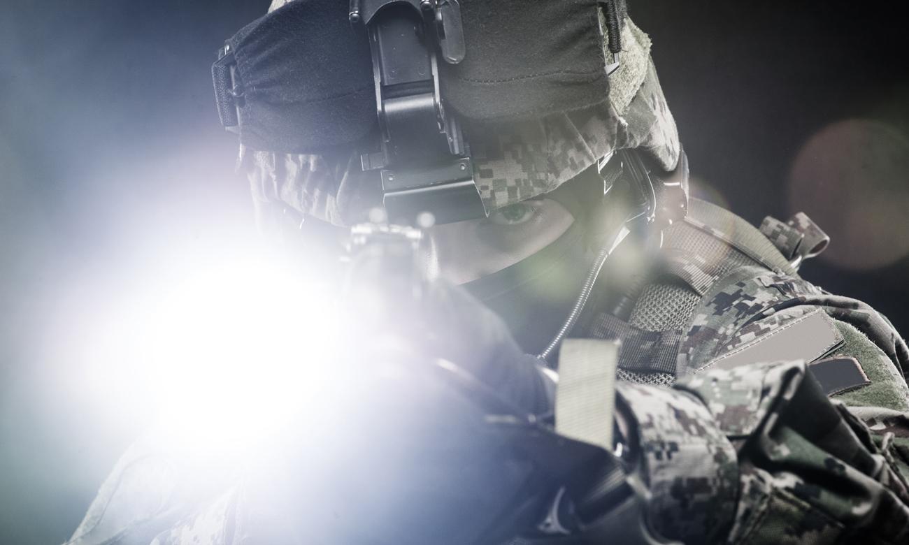 Żołnierz z wycelowanym karabinem i latarką