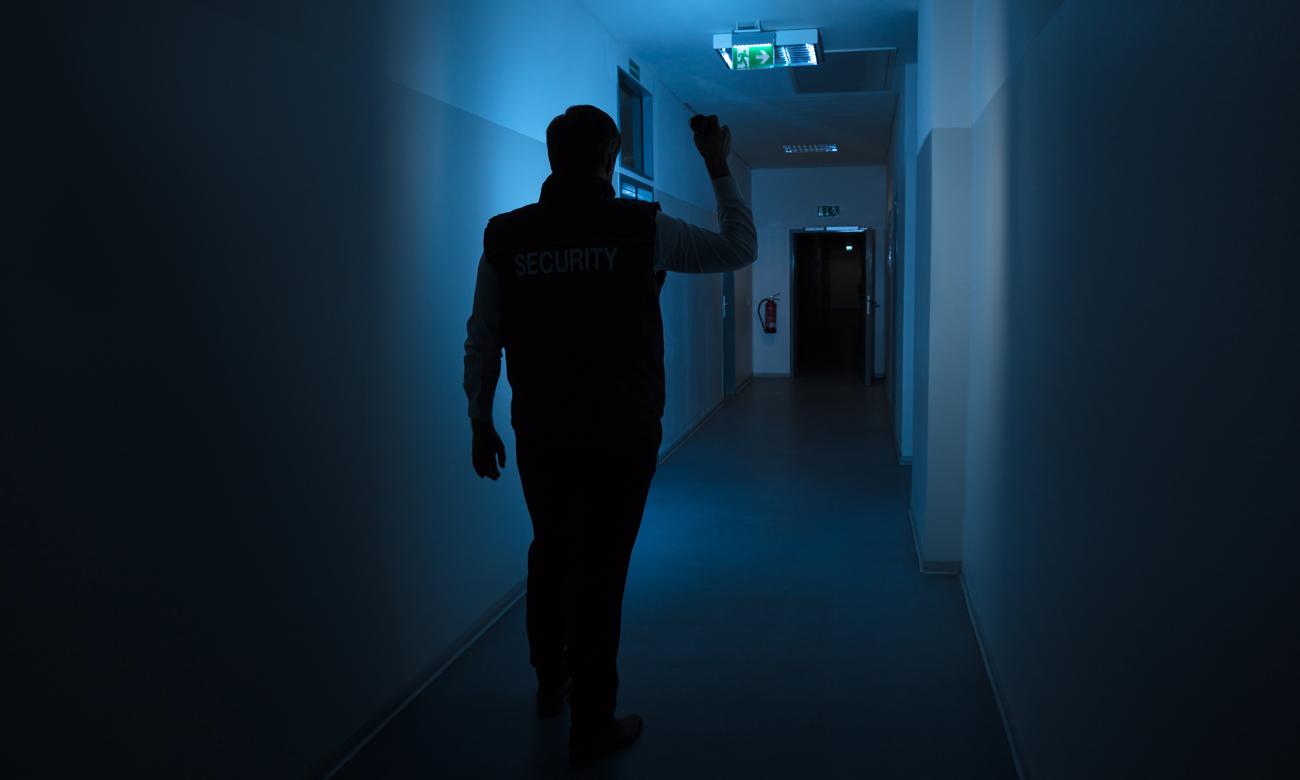 Ochroniarz z latarką w korytarzu