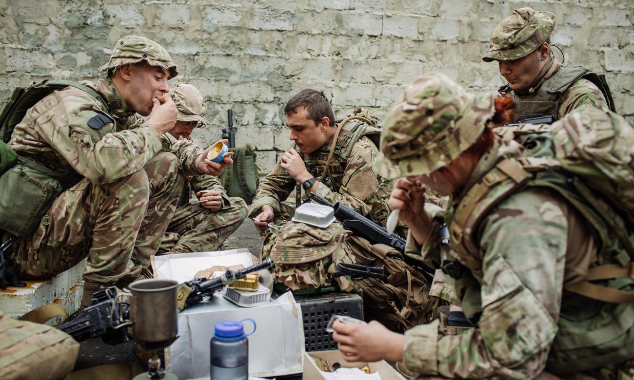 Żołnierze na polu walki jedzący konserwy