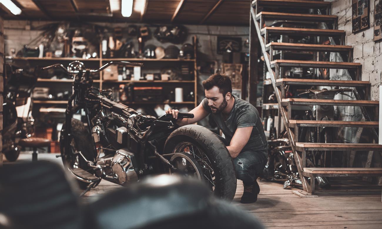 Człowiek naprawiający motocykl