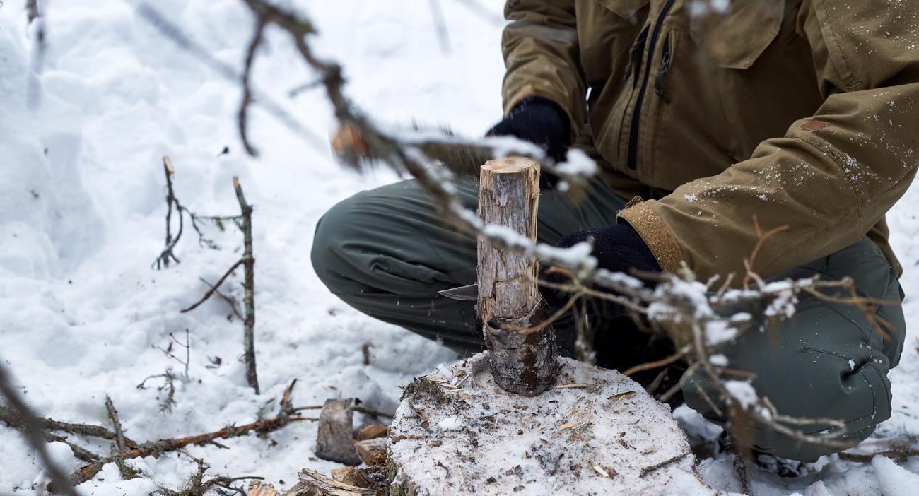 Czlowiek w terenie rozłupujący drewno