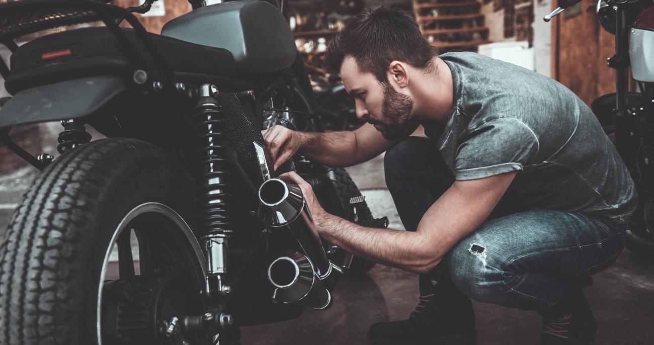 Mężczyzna naprawiający motocykl w swoim garażu multitool swisstool 115 mm